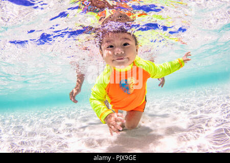 Baby swimming in ocean - Stock Photo