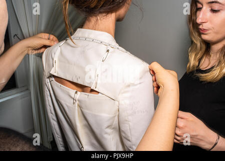 Fit model in fitting of tailored jackets before fashion show - Stock Photo