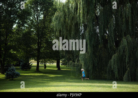 Boy playing under willow tree - Stock Photo