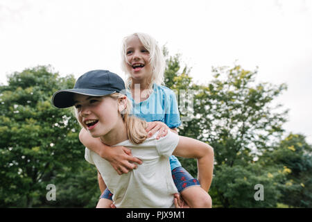 Children playing piggyback in park - Stock Photo