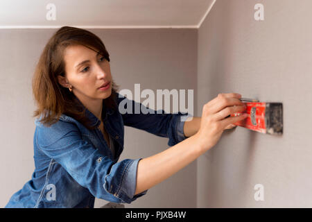 Home improvement. Beautiful women making a mark on wall with level. - Stock Photo