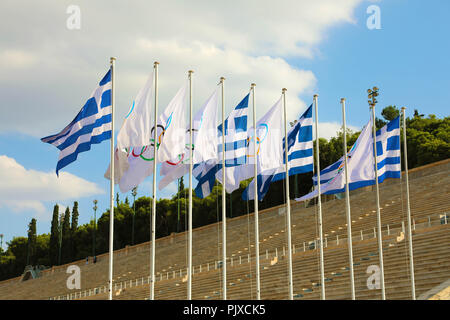 Flags of Greece and flags of Olympic games wave outside of Panathenaic Stadium in Athens, Greece on July 18, 2018 - Stock Photo