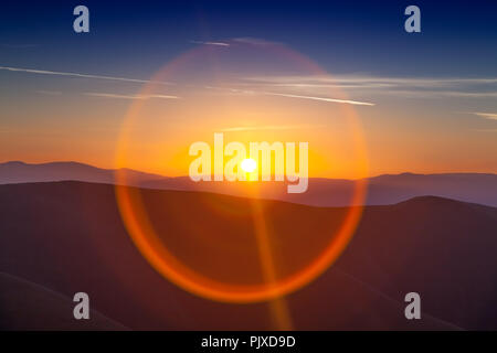 Circle sun reflexion at sunset over the mountains - Stock Photo