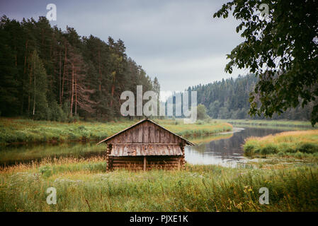 A log cabin on the river bank among the pines, in autumn - Stock Photo