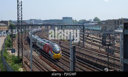 London, England - May 28, 2018: A Virgin Rail Group passenger train heading north at Primrose Hill, a short distance outside Euston railway station - Stock Photo