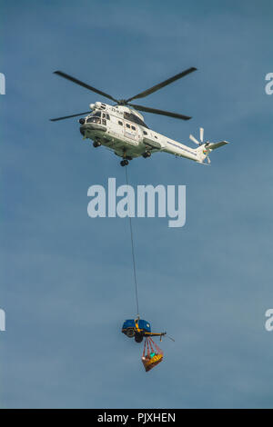 Rescue helicopter bringing supplies to the ship run aground on Sheffield Beach, near Durban, South Africa. - Stock Photo