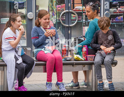 Children eating shop bought fast food while shopping in Bristol, England, UK - Stock Photo