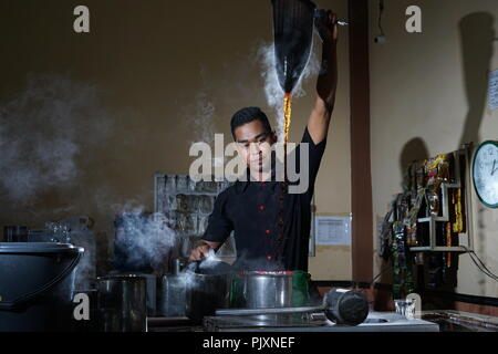 Traditional process of Aceh coffee making by Barista at Local Coffee Shop - Stock Photo