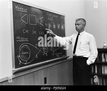 Langley Research Center, VA - (FILE) -- John C. Houbolt at blackboard, showing his space rendezvous concept for lunar landings on July 24, 1962. Lunar Orbital Rendezvous (LOR) would be used in the Apollo program. Although Houbolt did not invent the idea of LOR, he was the person most responsible for pushing it at NASA. Credit: Bob Nye - NASA via CNP /MediaPunch - Stock Photo