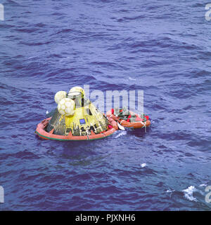 Houston, TX - (FILE) -- The Apollo 11 crew await pickup by a helicopter from the USS Hornet, prime recovery ship for the historic Apollo 11 lunar landing mission on Thursday, July 24,1969. The fourth man in the life raft is a United States Navy underwater demolition team swimmer. All four men are wearing Biological Isolation Garments (BIG). The Apollo 11 Command Module 'Columbia,' with astronauts Neil A. Armstrong, Michael Collins, and Edwin E. Aldrin Jr. splashed down at 11:49 a.m. (CDT), July 24, 1969, about 812 nautical miles southwest of Hawaii and only 12 nautical miles from the USS Horne - Stock Photo