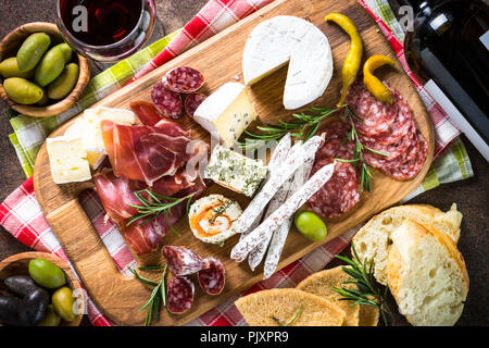 Antipasto - sliced meat, ham, salami, cheese, olives, ciabatta on wooden board. Top view. - Stock Photo