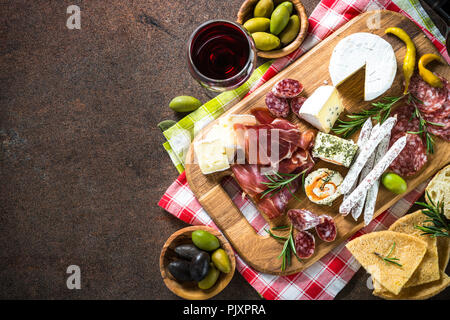 Antipasto - sliced meat, ham, salami, cheese, olives, ciabatta on wooden board at stone table. Top view copy space. - Stock Photo