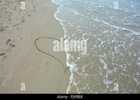 Heart in the sand painted with wave to the center of the heart - Stock Photo