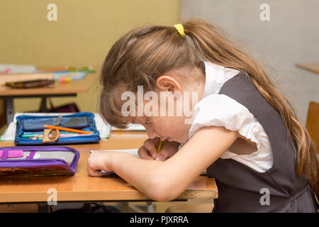 A schoolgirl with a wrong posture at the lesson writes in a notebook - Stock Photo