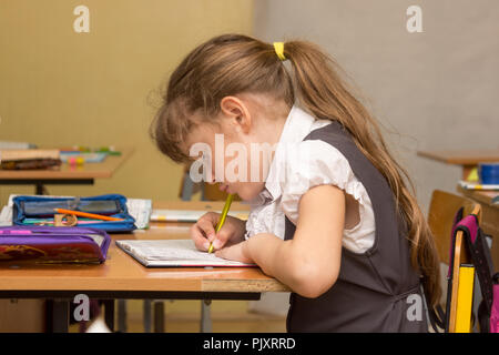A schoolgirl in a lesson crouched writes in a notebook - Stock Photo