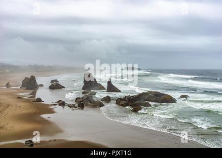 Bandon Beach overlook landscape with sea stacks or rocky outcrops along the coastline on an overcast rainy day, Oregon Coast, USA. - Stock Photo