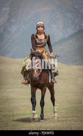 Lake Issyk-Kul, Kurgyzstan, 6th September 2018: young nomad lady with a bow and and arrows on a horse in the nature - Stock Photo