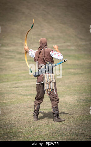 Lake Issyk-Kul, Kurgyzstan, 6th September 2018: young nomad shooting arrows in the nature - Stock Photo