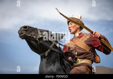Lake Issyk-Kul, Kurgyzstan, 6th September 2018: young nomad with a bow and and arrows on a horse in the nature - Stock Photo