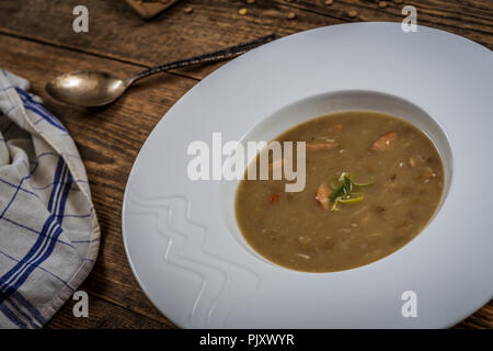 Brown Lentil sop with sausage on wood table - Stock Photo