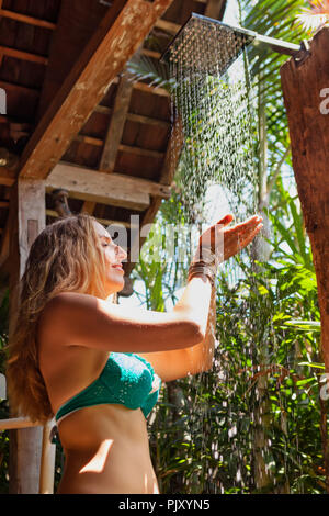 Attractive young girl takes shower. Woman stand under falling water drops in outside bathroom on open veranda with garden view in luxury villa - Stock Photo
