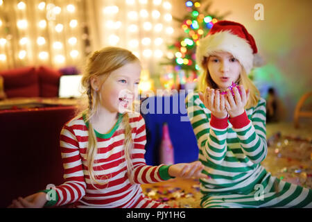 Two adorable sisters celebrating New Years eve in beautifully decorated room at home. Family having fun under Christmas tree at wonderful Xmas time. - Stock Photo