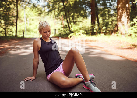 Fit young blonde woman in sportswear sitting alone on a forest path taking a break from a run - Stock Photo