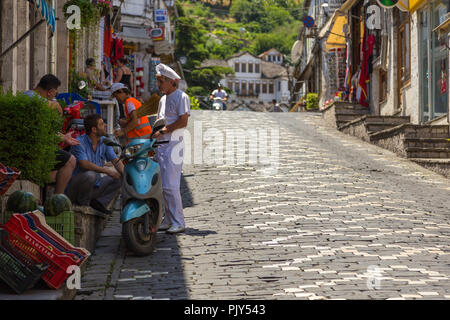 Gjirokaster, Albania- 28 June 2014: People on the main street of historic town Gjirokasteron in Gjirokaster. World Heritage Site by UNESCO. Called the - Stock Photo