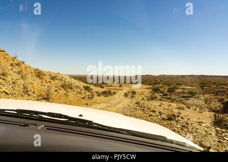 Woman's legs leaning out from car standing on gravel road in the Namib desert, Namib Naukluft National Park, main travel destination in Namibia, Afric - Stock Photo