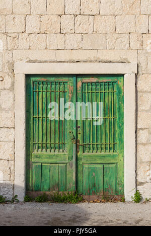 Old weathered green wooden door in stone wall - Stock Photo