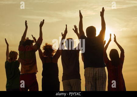 People raising hands up at the sky. - Stock Photo
