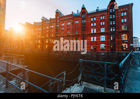 A red brick multi-storey houses of Speicherstadt Hamburg. Famous landmark of old red brick buildings in golden sunset light. Scenic evening view with canal handrail in foreground - Stock Photo
