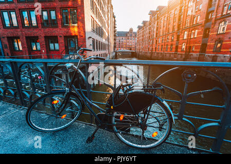 Old bicycle parked against iron hand railing on bridge in Hamburg warehouse district - Stock Photo
