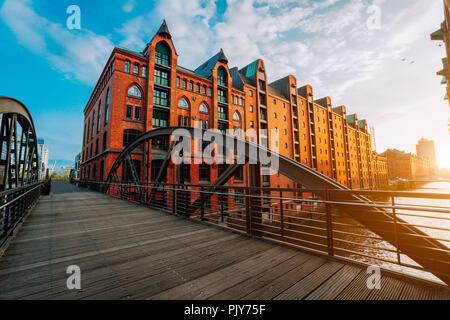 Pedestrian arch bridge over canals in the Speicherstadt of Hamburg. Warm golden hour sunset light on red bricks buildings