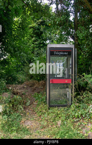 Secluded phone booth on a country lane - Stock Photo