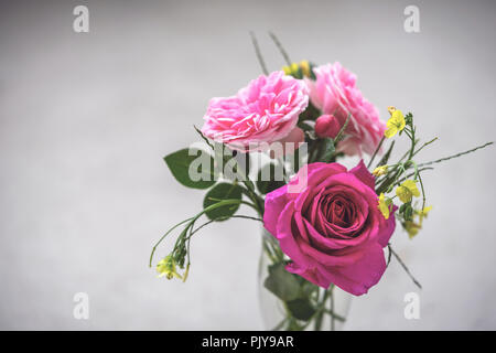 A bouquet of pink roses and yellow meadow buttercup flowers in a vase against grey background - Stock Photo