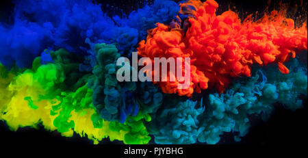 Mix of coloured inks in water on black background. Abstract colored background