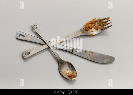 A close up view of dirty silver small spoon, knife and fork crossed over each other on a isolated white background - Stock Photo