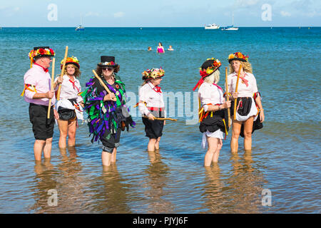 Swanage, Dorset, UK. 9th September 2018. Crowds flock to the 2nd day of the Swanage Folk Festival to see the dance groups and music along the seafront. Lovely warm sunny weather enticed some dancers to dance in the sea at the end of a wonderful weekend.  Morris dancers, members of Phoenix Morris dancing in the sea with member of Wicket Brood Border Morris. Credit: Carolyn Jenkins/Alamy Live News - Stock Photo