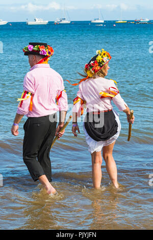 Swanage, Dorset, UK. 9th September 2018. Crowds flock to the 2nd day of the Swanage Folk Festival to see the dance groups and music along the seafront. Lovely warm sunny weather enticed some dancers to dance in the sea at the end of a wonderful weekend.  Morris dancers, members of Phoenix Morris dancing in the sea. Credit: Carolyn Jenkins/Alamy Live News - Stock Photo