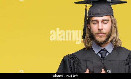 Young handsome graduated man with long hair over isolated background smiling with hands on chest with closed eyes and grateful gesture on face. Health - Stock Photo