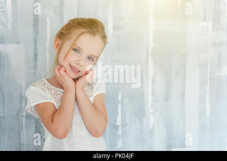 Sweet happy little girl in blank white t-shirt standing against grey textured wall background Childhood, schoolchildren, youth, relax concept - Stock Photo