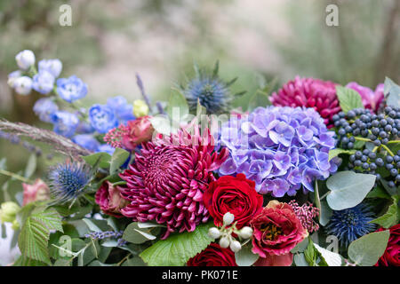 Elongated floral arrangement in vintage metal vase. table setting. Blue and red color. Gorgeous bouquet of different flowers. Park on background - Stock Photo