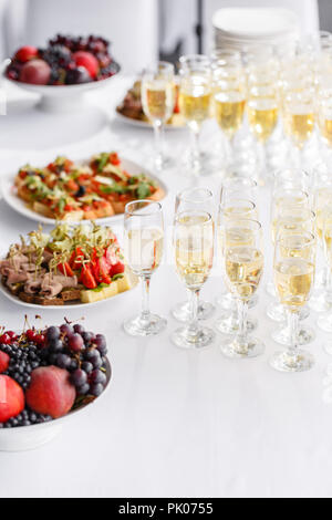 solemn happy new year banquet. Lot of glasses champagne or wine on the table in restaurant. buffet table with lots of delicious snacks. canapes, bruschetta, and little desserts on white plate - Stock Photo