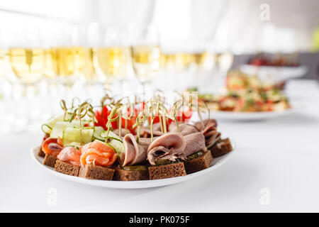 rye bread sandwiches, canapes, bruschetta on white plate. solemn banquet. Lot of glasses champagne or wine on the table in restaurant. buffet table with lots of delicious snacks. - Stock Photo