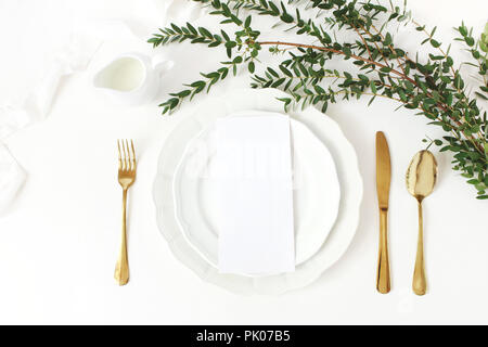 Festive wedding, birthday table setting with golden cutlery, eucalyptus parvifolia branch, porcelain plate, milk and silk ribbon. Blank card mockup. Rustic restaurant menu concept. Flat lay, top view - Stock Photo