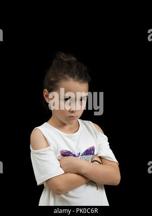 Young Caucasian girl with displeased gesture and arms crossed isolated over black. - Stock Photo