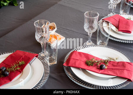 A lunch table set with under plates, lovely grey and white plates, red serviette, small decorative tree branch, two grapes with floral and fruit decor - Stock Photo