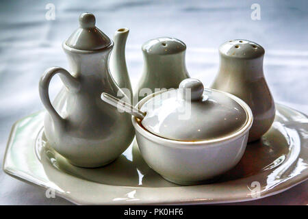 Close up of A simple white ceramic set of cream & sugar set with matching salt & pepper shakers in a backlit scene on a  white table cloth on table - Stock Photo
