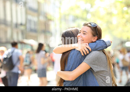 Friends meeting and hugging in the street - Stock Photo